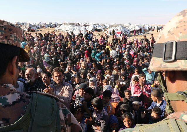 Syrian refugees, stuck between the Jordanian and Syrian borders, wait to cross into Jordan, at the Hadalat border crossing, east of the Jordanian capital Amman, on January 14, 2016