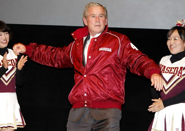 Former U.S. President George W. Bush, center, shows a pitching form, wearing a university's baseball jacket, during his visit to Waseda University in Tokyo, Japan.