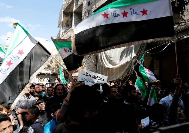 Syrian civilians and activists wave their national flags on the outskirts of the capital Damascus, on March 4, 2016.