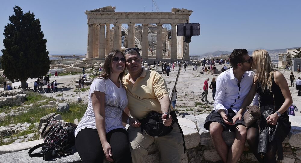 Tourists take pictures while visiting the Acropolis in Athens on April 3, 2015