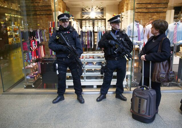 A passenger chats to armed police officers on patrol after Eurostar trains to Brussels were cancelled at St Pancras station in central London, Britain.