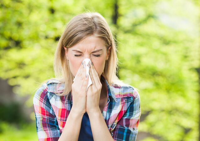 Woman with allergy symptom blowing nose.