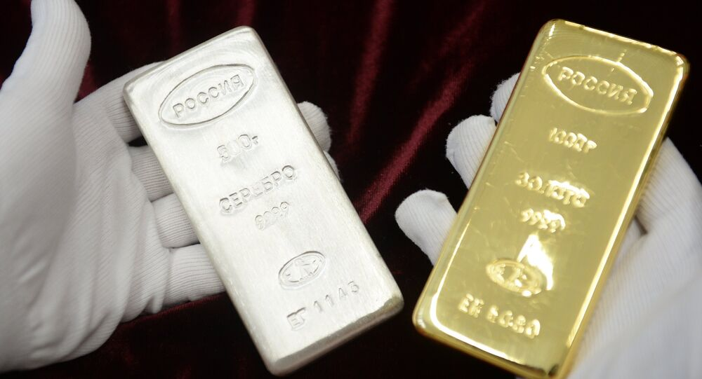A worker holds a gold bar and a silver bar produced during the opening of a new bank bar manufacturing line at the Yekaterinburg Plant for Non-Ferrous Metals Processing, in the town of Verkhnyaya Pyshma, Sverdlovsk region.