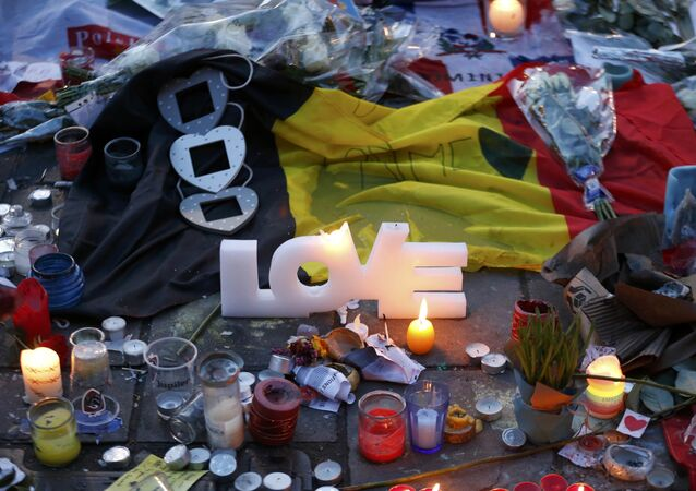 Candles and a flag are seen at the Place de la Bourse as people pay tribute to the victims of Tuesday's bomb attacks in Brussels, Belgium, March 25, 2016.