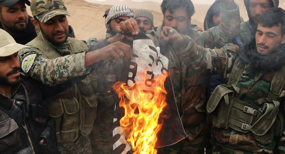 Desert Falcons militia burn a Daesh flag taken down from the citadel of Palmyra taken over from the terrorists.