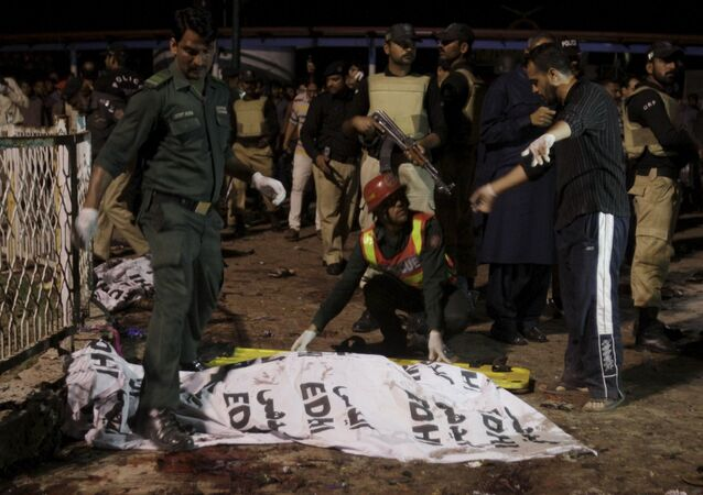 Rescue workers move a body from the site of a blast outside a public park in Lahore, Pakistan