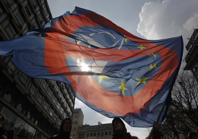A man waves an anti NATO and EU flag during an anti NATO rally in downtown Belgrade, Serbia, March 27, 2016.