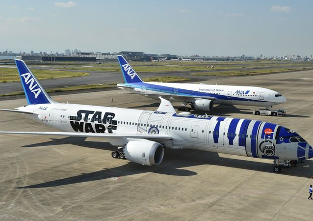 An All Nippon Airways (ANA) Boeing 787-9 aircraft in the livery of Star Wars droid character R2-D2 (front) is seen on the tarmac at Tokyo's Haneda airport on October 14, 2015