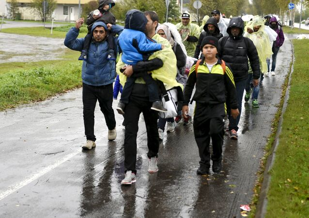 Refugees walk through the pouring rain from a public transport centre to the Lapland refugee reception centre in Tornio, northwestern Finland, in September 2015.