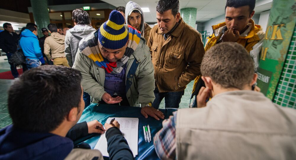 Refugees register their names as they arrive to Stockholm central mosque on 15 October 2015 after a bus journey from the southern city of Malmo.