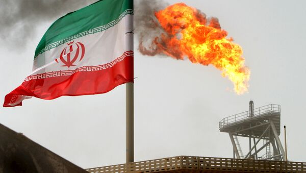 A gas flare on an oil production platform in the Soroush oil fields is seen alongside an Iranian flag in the Persian Gulf, in this July 25, 2005 file photo - Sputnik International