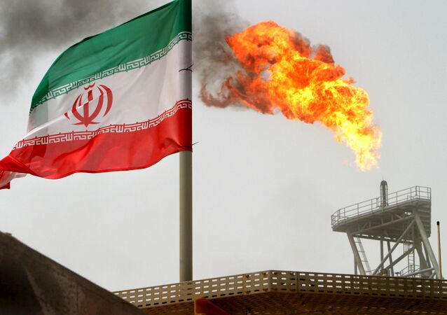 A gas flare on an oil production platform in the Soroush oil fields is seen alongside an Iranian flag in the Persian Gulf, in this July 25, 2005 file photo