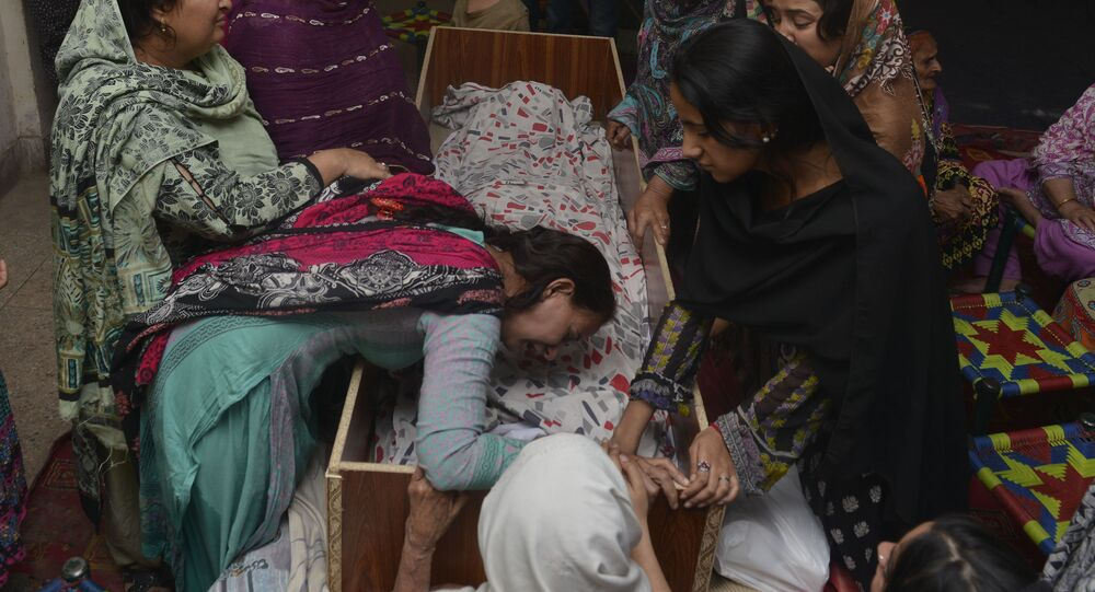 Pakistani relatives mourn over the body of a victim during a funeral following an overnight suicide bombing in Lahore on March 28, 2016