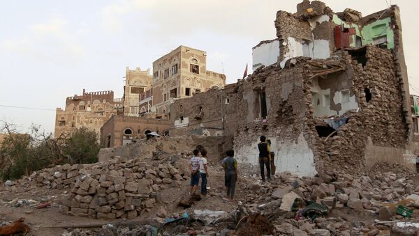 Yemeni children look on March 23, 2016 at buildings that were damaged by air strikes carried out by the Saudi-led coalition over the past year in the UNESCO-listed old city of the Yemeni capital Sanaa - Sputnik International