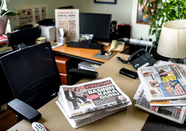 A picture taken on November 27, 2015 in Istanbul, shows newspapers at the office of Cumhuriyet Daily newspaper's Editor in Chief Can Dundar, as people demonstrate outside the headquarters after the arrest of Dundar.