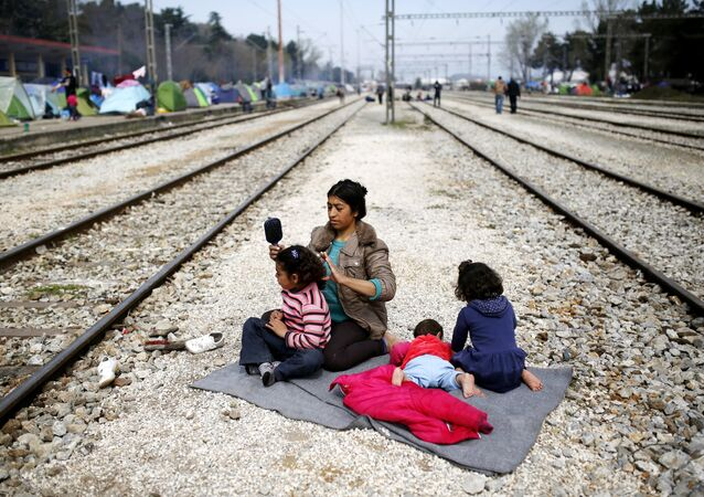 A woman sits with her children along railway tracks at a makeshift camp for migrants and refugees at the Greek-Macedonian border near the village of Idomeni, Greece, March 29, 2016.