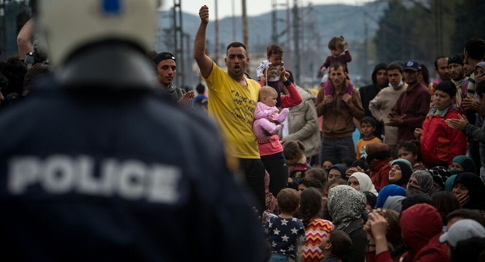 Yazidi refugees protest to call for the reopening of the borders at a makeshift camp at the Greek-Macedonian border near the village of Idomeni on March 21, 2016