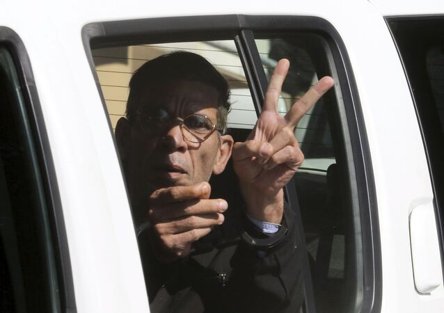 A man named Seif Eldin Mustafa, who was arrested after he hijacked an EgyptAir flight, which was forced to land in Cyprus on Tuesday, gestures as he is transferred by Cypriot police from a court in the city of Larnaca, Cyprus March 30, 2016.