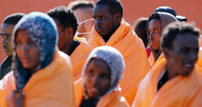 Migrants stand in line after disembarking from the Norwegian vessel Siem Pilot at Pozzallo's harbour, Italy, March 29, 2016.