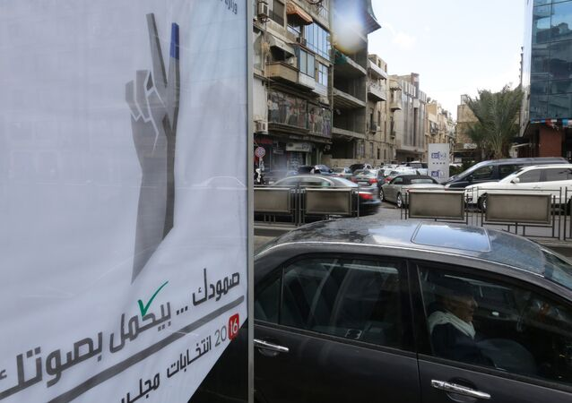 Syrians drive past a billboard for the upcoming parliamentary elections in the capital Damascus on March 15, 2016
