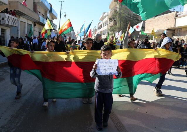 Kurdish children hold a flag of the Kurdish People's Protection Units (YPG) political wing, the Democratic Union Party (PYD), and banners during a demonstration against the exclusion of Syrian-Kurds from the Geneva talks in the northeastern Syrian city of Qamishli on February 4, 2016