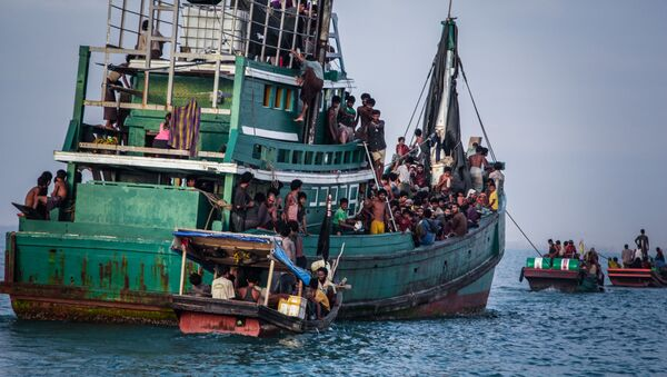 In this photo taken on May 20, 2015 shows Rohingya migrants resting on a boat off the coast near Kuala Simpang Tiga in Indonesia's East Aceh district of Aceh province before being rescued. Indonesia's foreign minister demanded answers from Canberra about claims Australian officials paid thousands of dollars to turn a boat back to Indonesia after Prime Minister Tony Abbott refused to deny the allegations - Sputnik International