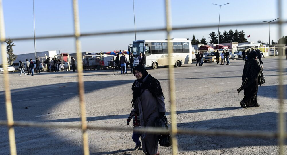 A Syrian woman and a child walks back towards the Syrian crossing, on February 8, 2016 at Turkish Oncupinar border gate near Kilis, southern-central Turkey