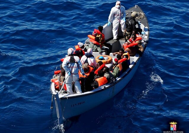 Migrants sit on a rescue boat during a rescue operation of migrants by Italian Navy vessels in this March 18, 2016 handout picture.