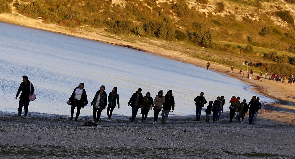 Refugees walk along a beach before trying to travel to the Greek island of Chios from the western Turkish coastal town of Cesme, in Izmir province, Turkey, in this March 5, 2016 file photo.