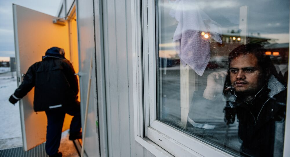 A refugee looks through a window at the arrival centre for refugees near the town on Kirkenes in northern Norway