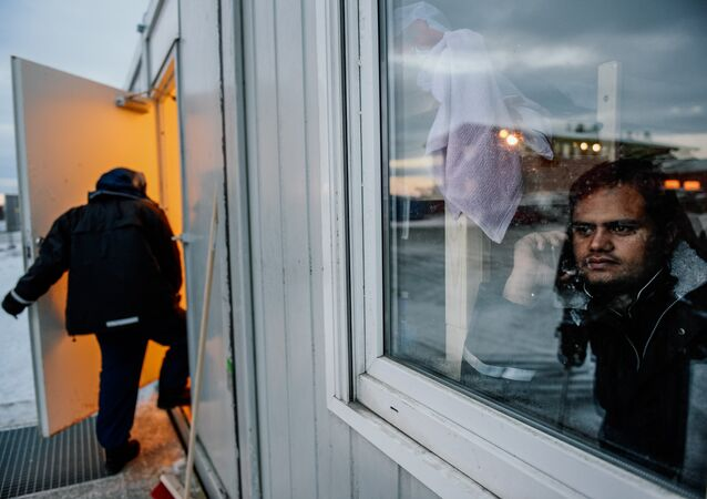 A refugee looks through a window as he speaks on the phone in the sleeping facilities at the arrival centre for refugees near the town on Kirkenes in northern Norway close to the border with Russia on November 11, 2015