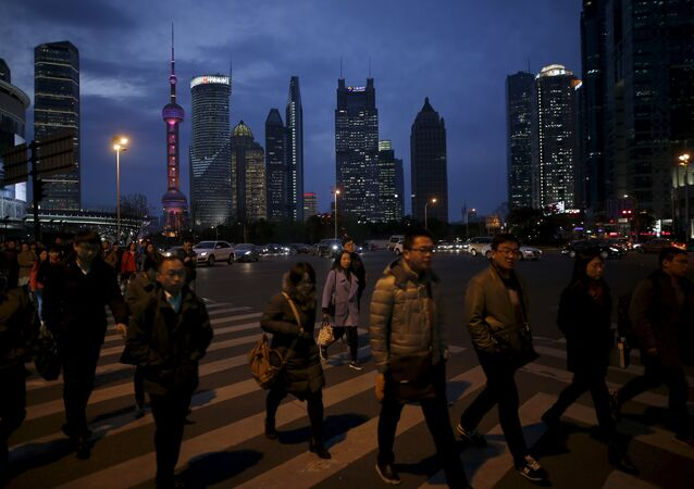 People cross a road after work in the financial district of Pudong in Shanghai, China, March 15, 2016