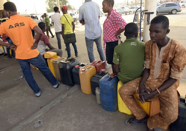 People queue to buy fuel with jerry cans at a filling station in Lagos, on December 1, 2015.