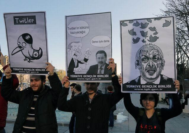 Members of the Turkish Youth Union hold cartoons depicting Turkey's Prime Minister Recep Tayyip Erdogan during a protest against a ban on Twitter, in Ankara, Turkey, Friday, March 21, 2014