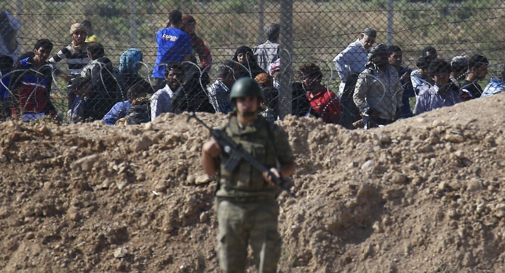 File photo of a Turkish army soldier guards the border area with Syria as in the background Syrian refugees wait in Syria in order to cross into Turkey, in Akcakale, southeastern Turkey, Monday, June 15, 2015