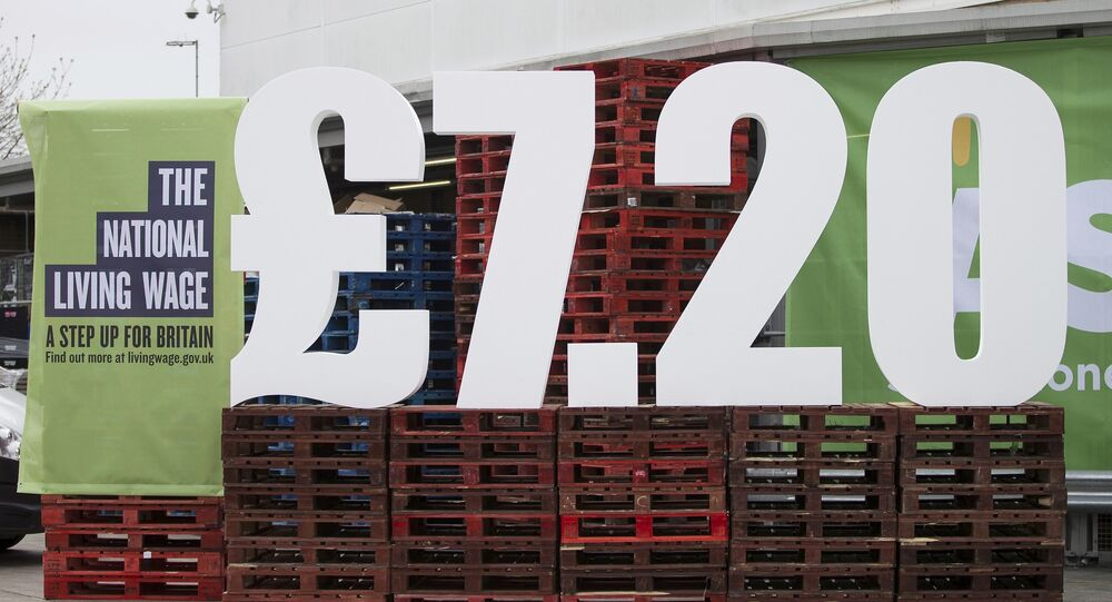 Britain's new living wage is displayed outside an Asda Supermarket in Trafford, Manchester, April 1, 2016