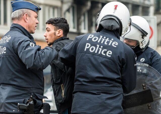 Policemen detain a man in the Molenbeek neighborhood in Brussels, Belgium