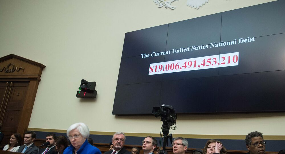 A screen shows the US national debt before US Federal Reserve chair Janet Yellen (front L) testifies before the House Financial Services Committee on Capitol Hill in Washington, DC, on February 10, 2016.
