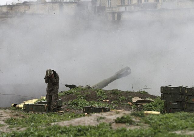 An Armenian serviceman of the self-defense army of Nagorno-Karabakh launch artillery toward Azeri forces in the town of Martakert in Nagorno-Karabakh region