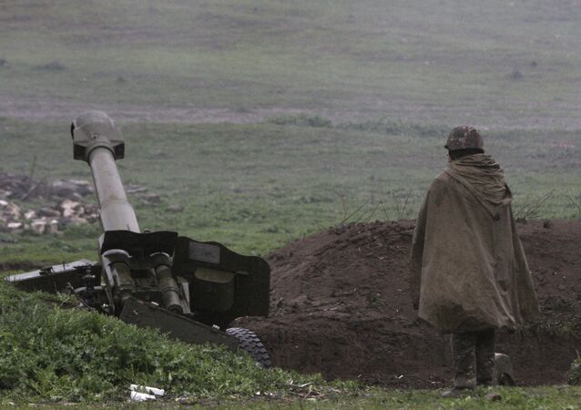 An Armenian soldier of the self-defense army of Nagorno-Karabakh stands near an artillery unit in the town of Martakert, where clashes with Azeri forces are taking place, in Nagorno-Karabakh region