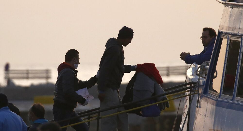 A Frontex officer (L) escorts a migrant as he boards on a Turkish-flagged passenger boat to be returned to Turkey, on the Greek island of Lesbos, April 4, 2016.