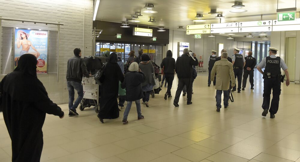 Policemen escort a group of refugees after their arrival at the airport in Hanover, central Germany, on April 4, 2016.