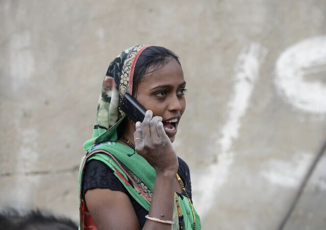 An Indian woman speaks on a mobile phone
