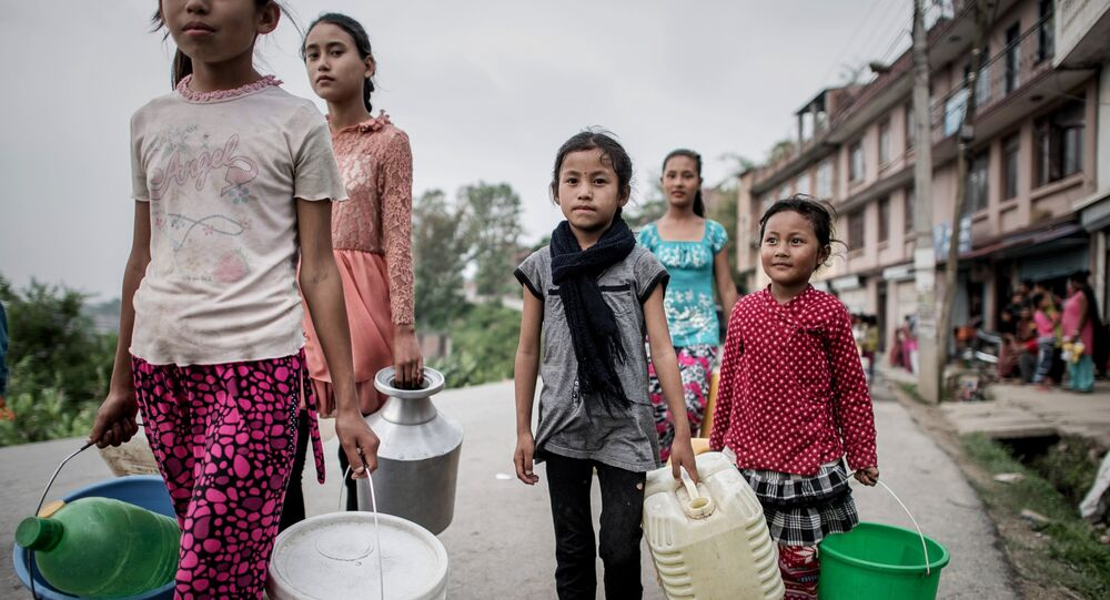 Children carry buckets to get water distributed as relief aid outside Bungamati village, in the outskirts of Kathmandu on May 8, 2015.