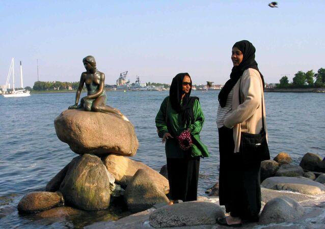 Somalian refugees living in Denmark pose by the Little Mermaid statue in Copenhagen
