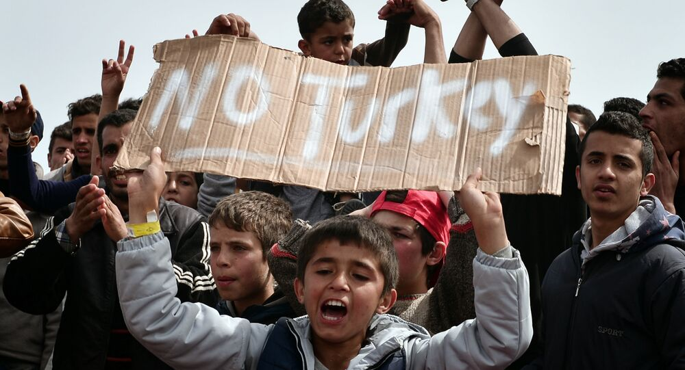 Refugees and migrants including children who left the Chios registration camp, shout slogans and hold placards reading 'No Turkey during a protest on April 3, 2016 as they camp out in the port of Chios.