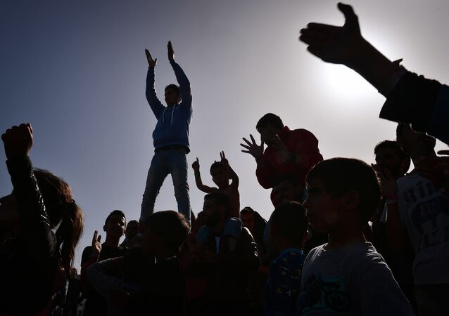 The silhouettes of Kurdish refugees who managed to leave the VIAL detention center on the island of Chios are seen as they protest against deportations to Turkey at the island's port where they are camping out on April 5, 2016.