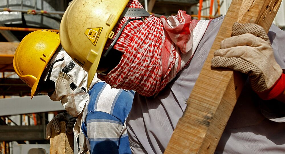 Foreign workers, covering their faces from dust and the blazing sun, work inside the Khouris central processiong oil facility that is still under construction in Saudi Arabia's desert, 160 kms east of the capital Riyadh (File)