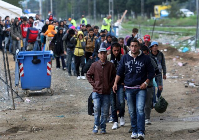 Migrants and refugees walk to cross Greek-Macedonian border near the village of Idomeni, in northern Greece on October 14, 2015