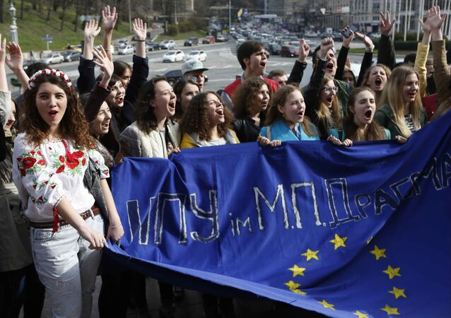 Ukrainian students hold a EU flag with a sign reading A pedagogical university, as they stand in a live chain in downtown Kiev, Ukraine, Tuesday, April 5, 2016. Ukrainian students gathered in Kiev to back Ukraine's cause on the eve of a Dutch referendum on an association deal between Ukraine and the EU